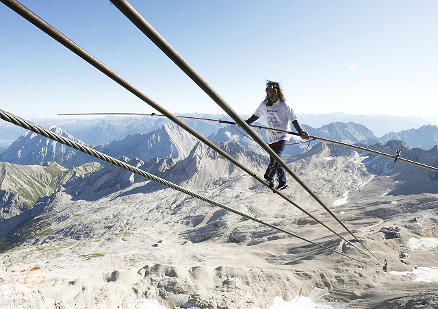 GARMISCH-PARTENKIRCHEN, GERMANY - AUGUST 30: Swiss Freddy Nock balances on the cable car ropeway in front of the Alps panorama on top of Germany's highest mountain Zugspitze on August 30, 2009 near Garmisch-Partenkirchen, Germany.  (Photo by Alexandra Beier/Bongarts/Getty Images)